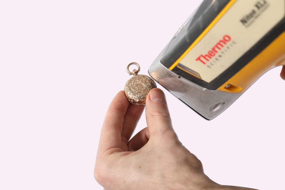 Expert testing purity of metal using a handheld metal analyser.